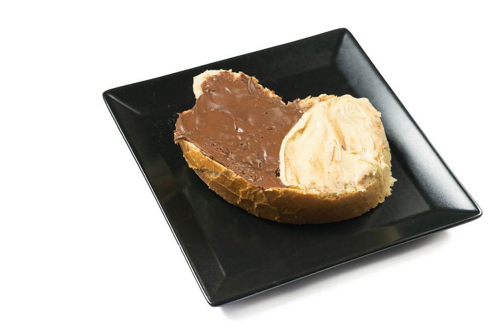 Brotscheibe mit dunkler und weißem Schokoladenaufstrich auf schwarzem eckigem Teller vor weissem Hintergrund
