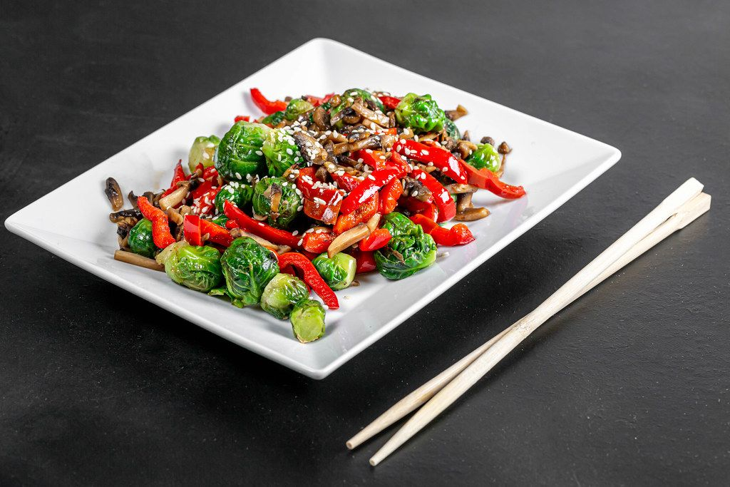 Brussels sprouts, sliced mushrooms and bell peppers with sesame seeds on a black background