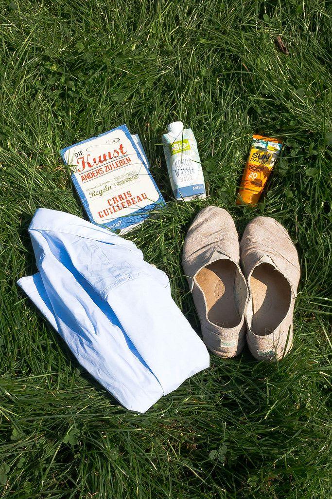 Buch, Kokoswasser, Sonnencreme, Hemd und leichtes, luftiges Schuhwerk