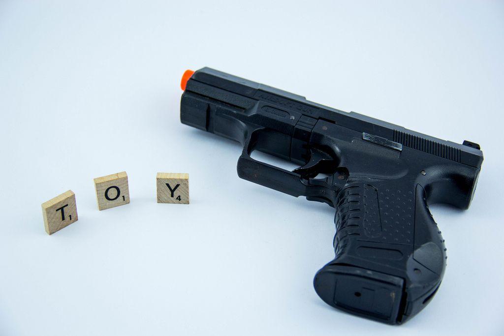 Buchstaben auf Holzquadraten bilden das Wort TOY neben Spielzeugwaffe auf weißem Hintergrund