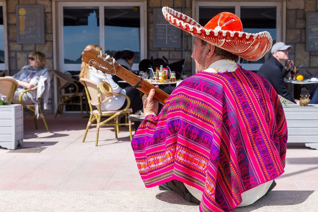 Bunt gekleideter Mann mit Sombrero und Poncho spielt Gitarre