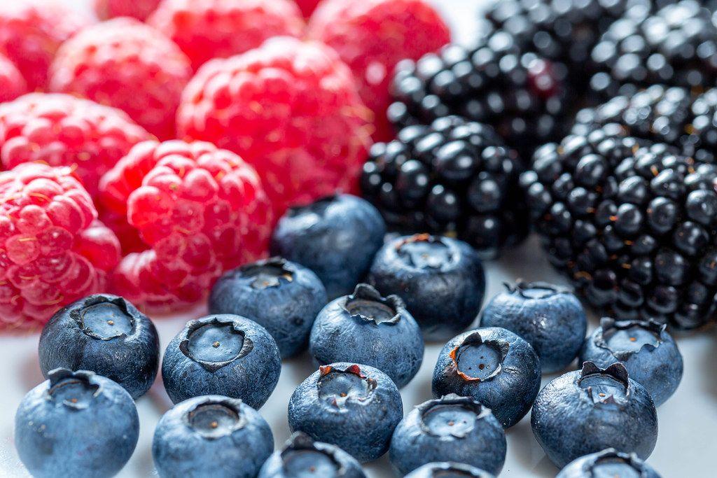 Bunte Beerenmischung mit blauen Heidelbeeren, roten Himbeeren und dunklen Maulbeeren