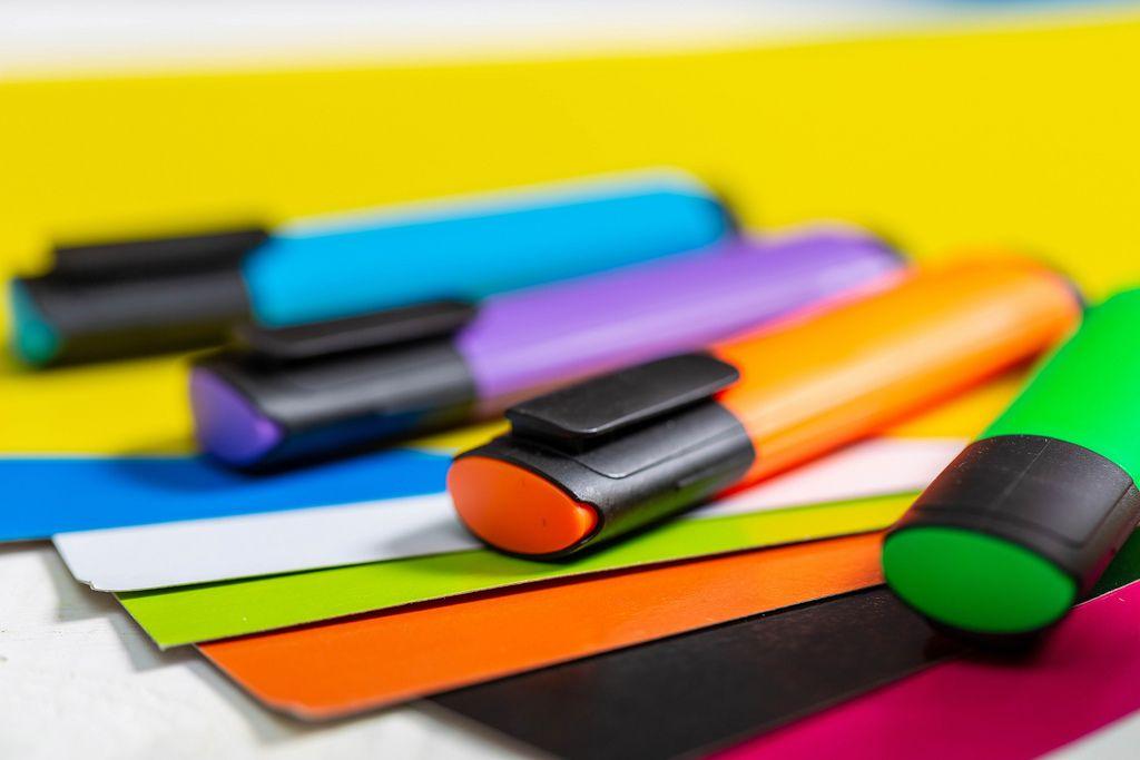 Bunte Textmarker in blau, grün, orange und violett liegen auf farbigen Papierbögen