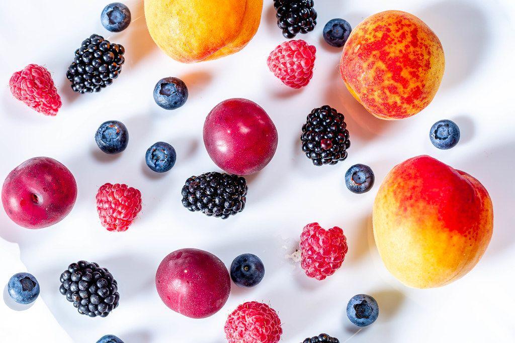 Buntes Obst wie Maulbeeren, Heidelbeeren,  Himbeere,  Pflaume und Aprikosen liegen auf einem weißen Hintergrund