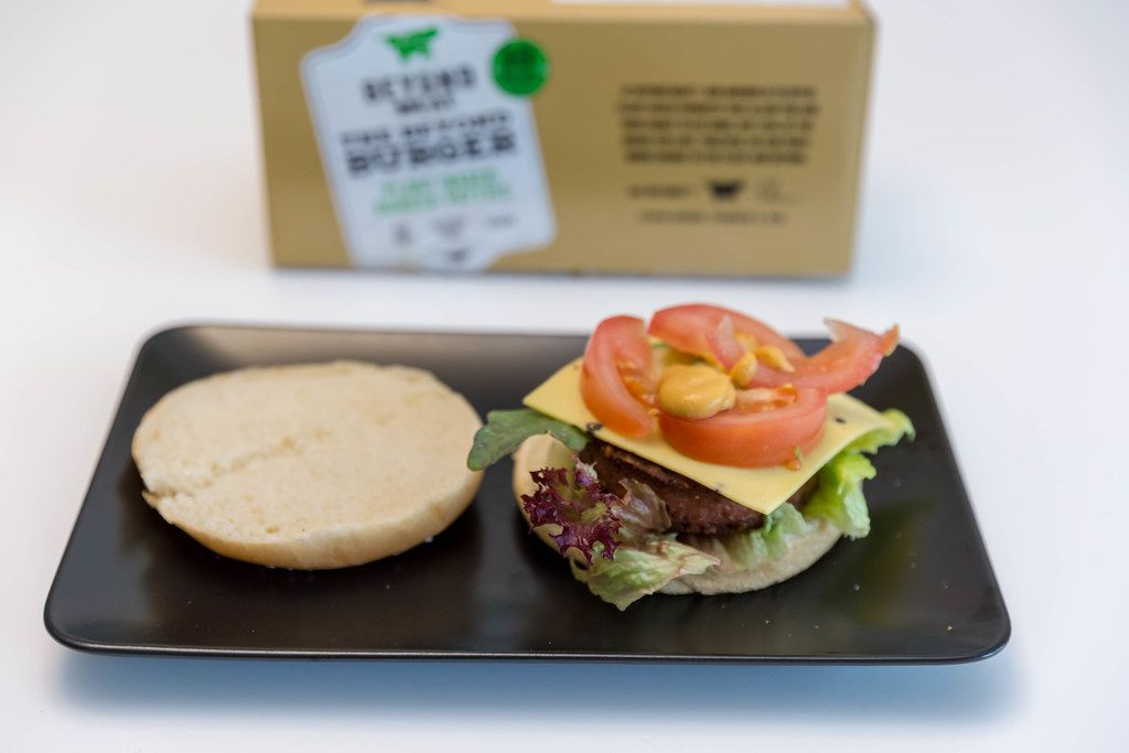 Burger bun with mixed salad, cheese, tomatoes and dip for a veggie burger of the Beyond Meat vegan and plant-based burger patties set