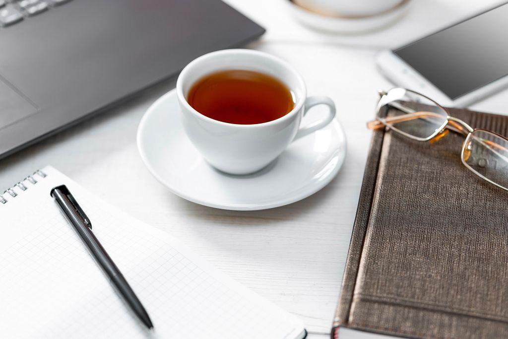 Büroszene mit Laptop und Smartphone, Buch, Notizheft, Schreiber, Brille und einer Tasse Tee