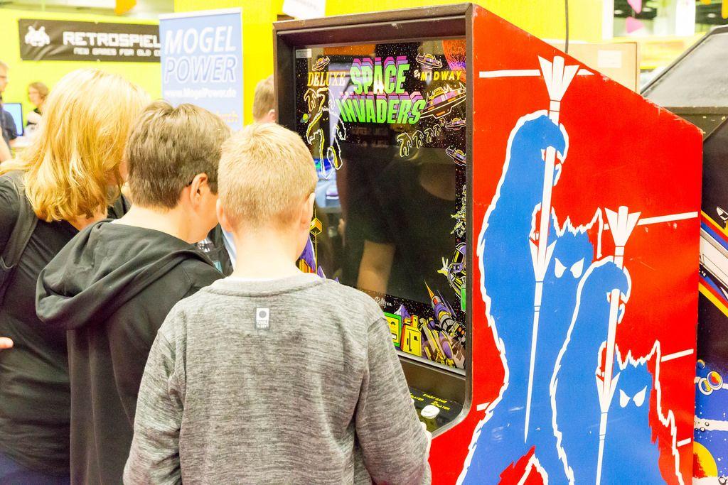 Burschen spielen Space Invaders auf einem Arcade-Automaten - Gamescom 2017, Köln