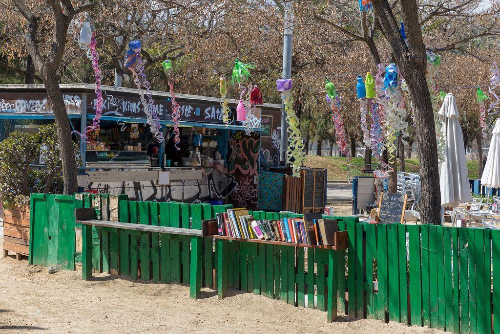 Café Gamar und öffentliche Mini-Bibliothek an einem grünen Zaun, unter Girlanden-Deko aus Plastikmüll im Barceloneta Park in Barcelona, Spanien