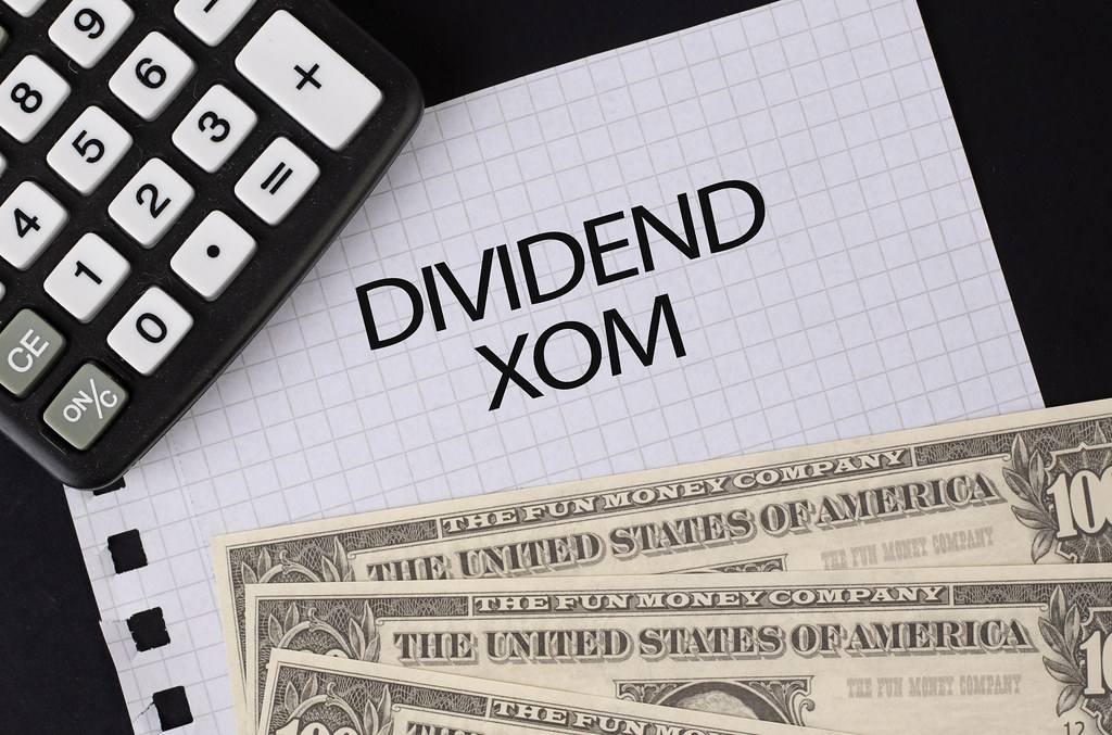 Calculator, money and Dividend XOM text on black table