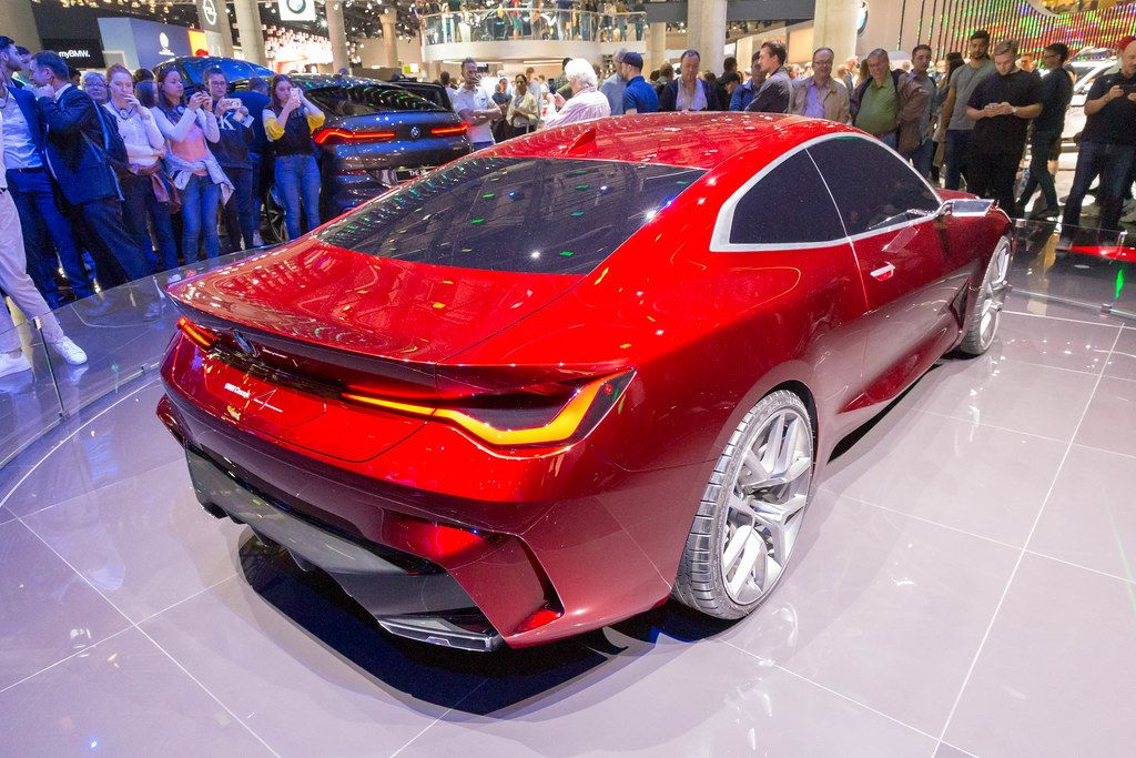 Car exhibition visitors taking pictures of red sports car by BMW Concept 4 Series Coupé