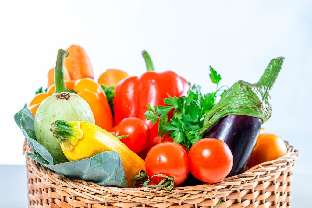 Carrots, bell peppers,balajan, tomatoes, zucchini and parsley in a wicker basket close-up (Flip 2019)