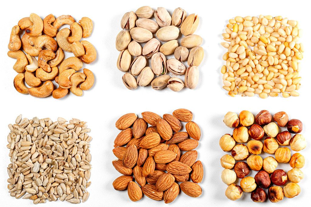 Cashew nuts, pistachios, pine nuts, almonds, hazelnuts and sunflower seeds on a white background