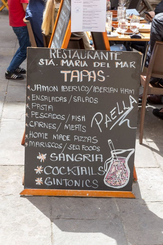 Chalkboard menu recommendation of the Santa Maria del Mar restaurant including Spanish specialties such as Iberian ham, tapas, paella and sangria on a street in Barcelona