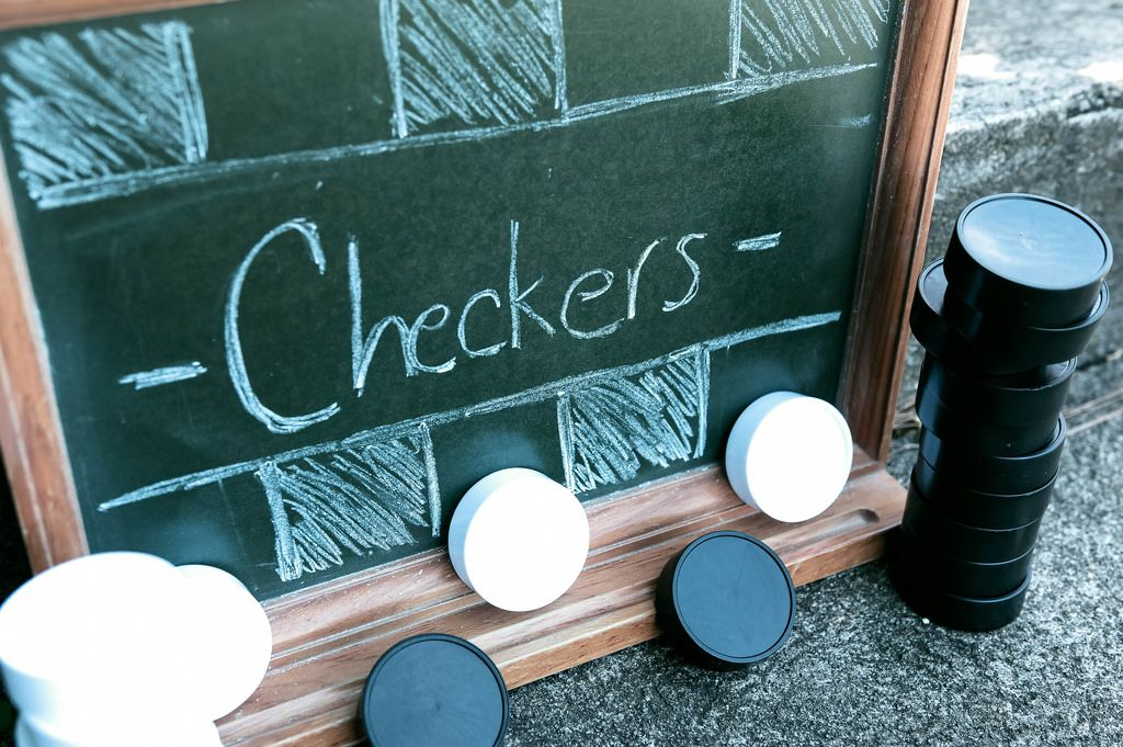 Checkers written on chalkboard and tokens around it