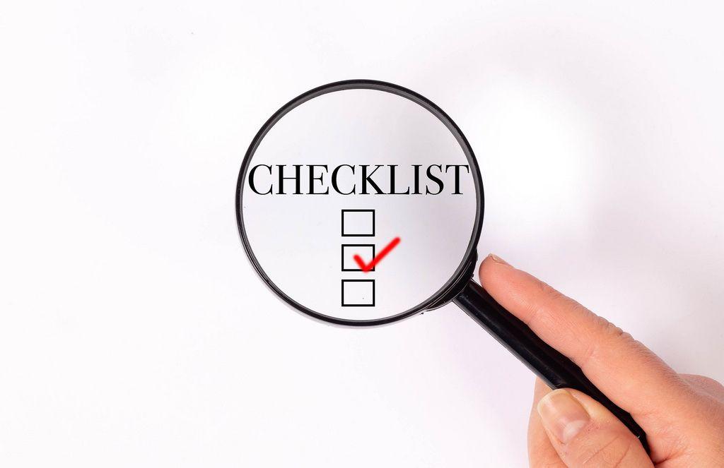 Checklist unter der Lupe auf weißem Hintergrund