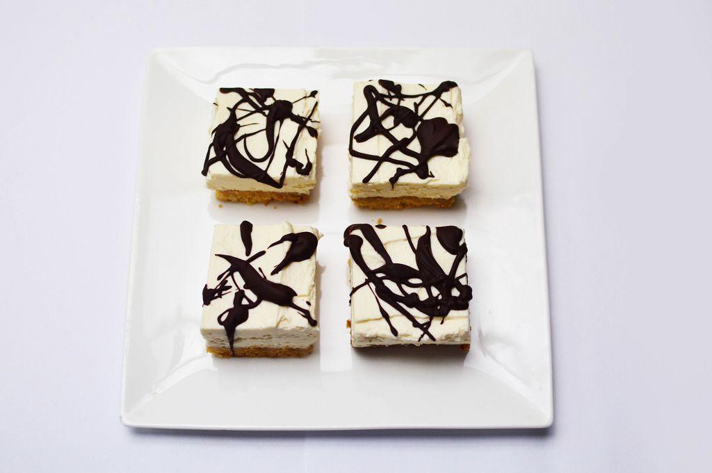 Cheesecake mit Schokoladensoße auf einem quadratischen Teller