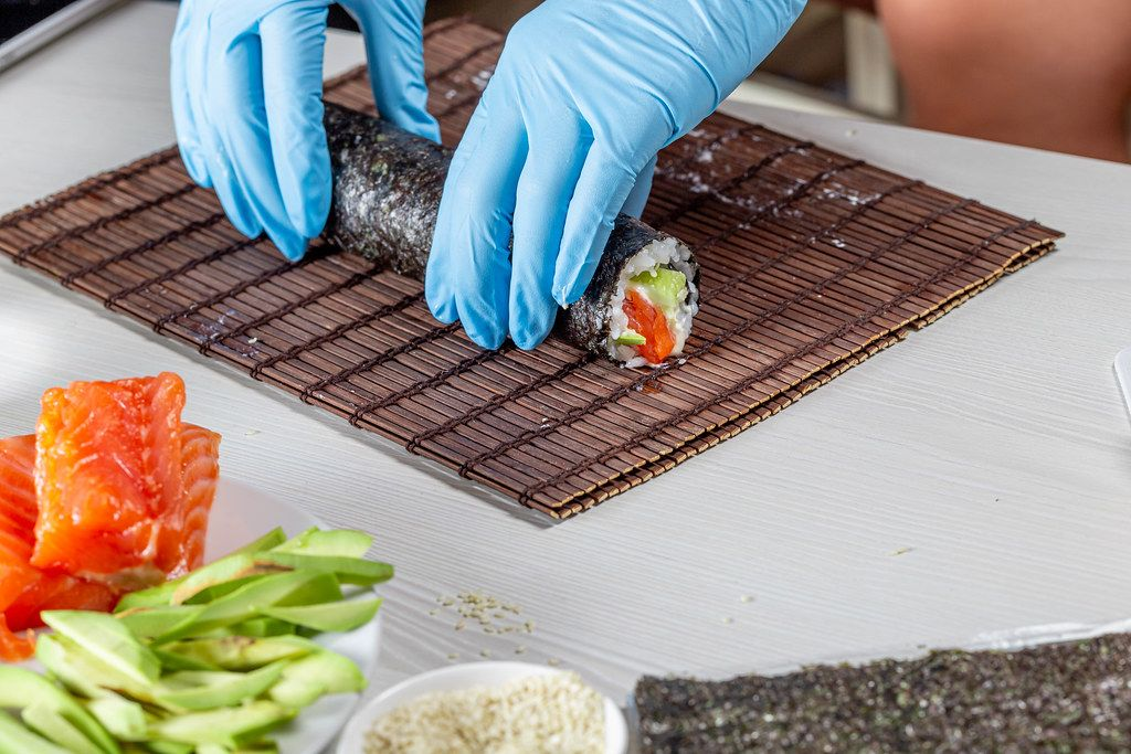Chef hands in disposable gloves cooking sushi at kitchen of home (Flip 2019)