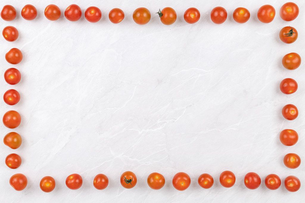 Cherry tomatoes frame on the grey marble table