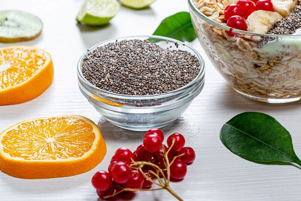 Chia seeds, fresh viburnum, sliced fruit and a bowl of oatmeal on a white wooden background