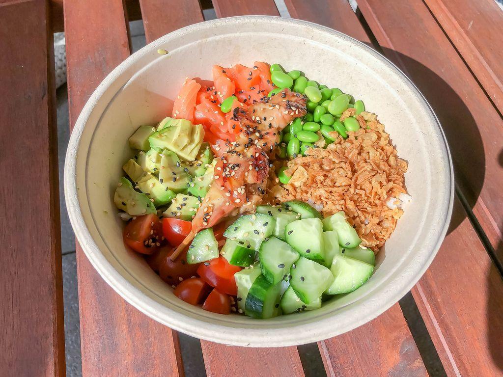 Chicken Teriyaki mit Avocado, Tomaten, Saubohnen, Rostzwiebel, Sushireis und Gurken in einer weißen Schale von Eat Simple