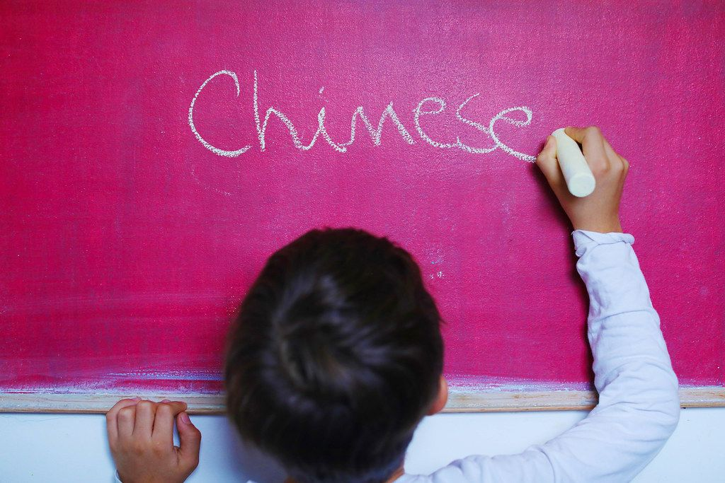 Child writes Chinese word on chalkboard, learning foreign language