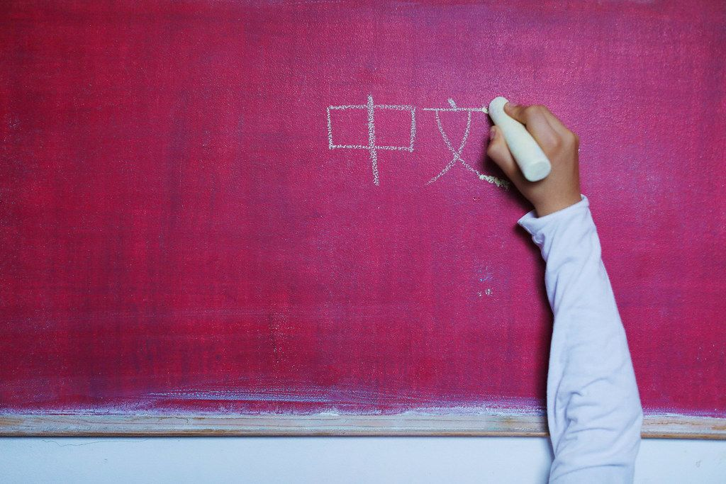 Child writes Chinese word with Chinese simplified characters on chalkboard, learning foreign language
