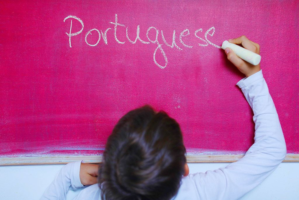 Child writes Portuguese word on chalkboard, learning foreign language