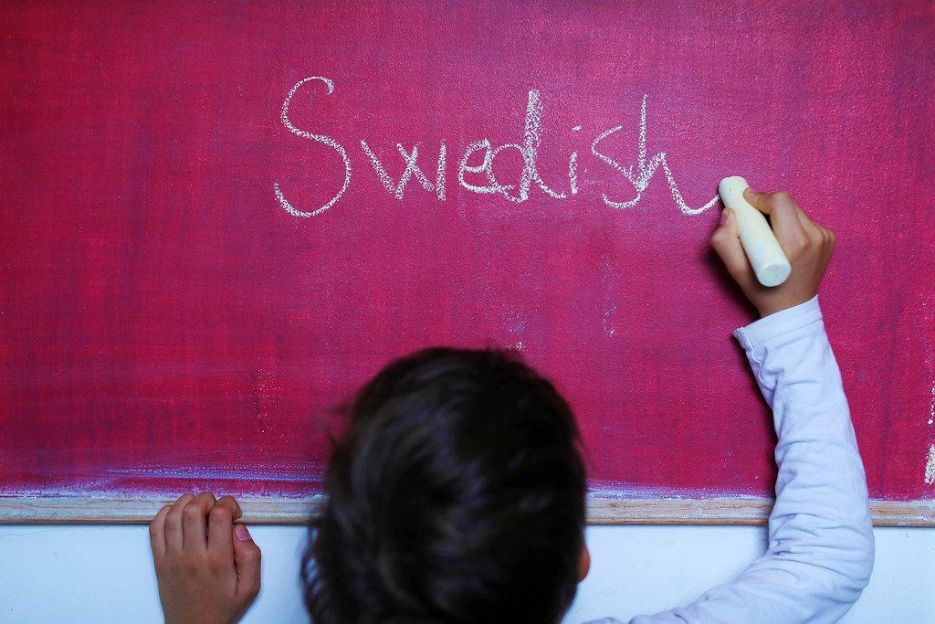Child writes Swedish word on chalkboard, learning foreign language