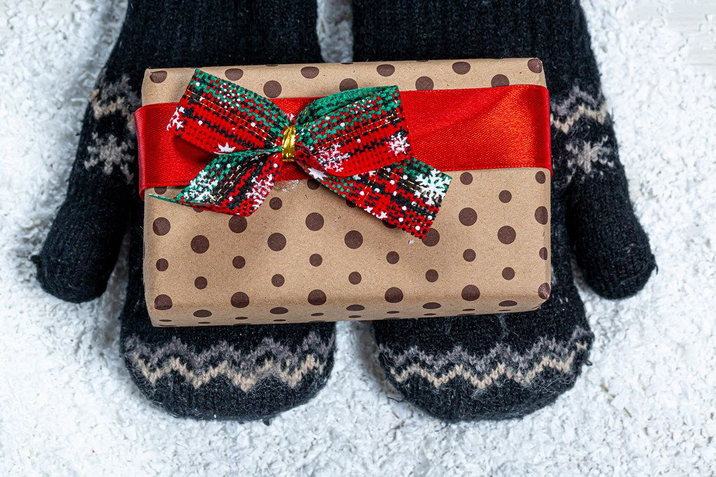 Children's hands in mittens are holding a gift on a snow background. View from above