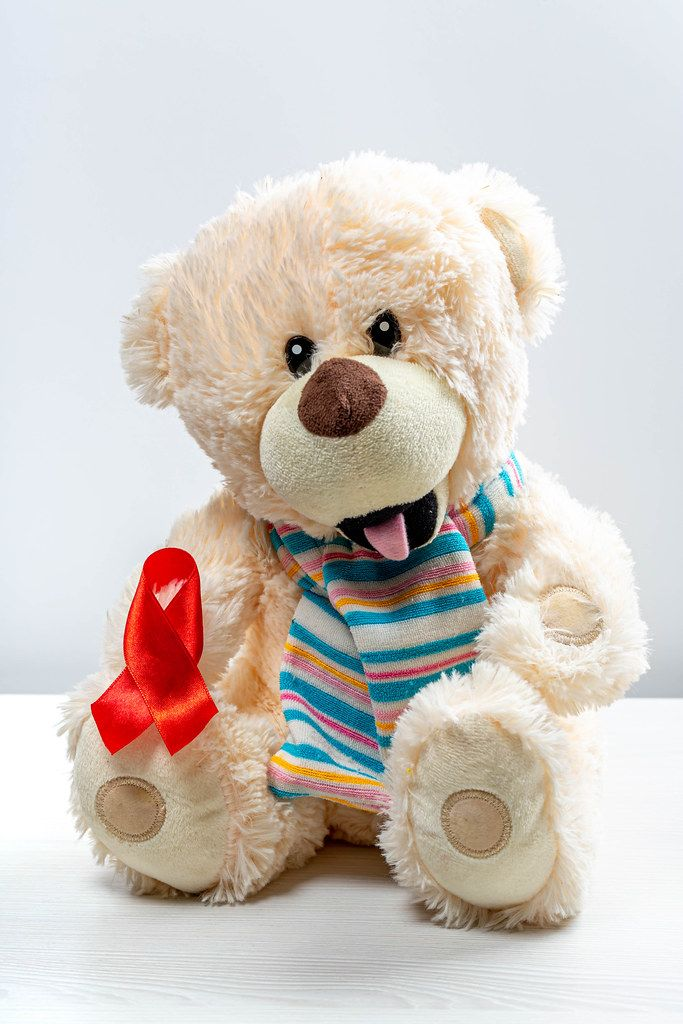 Children's toy bear with red ribbon as a symbol of the fight against children's cancer (Flip 2019)