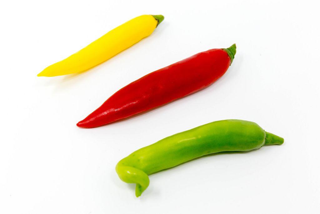Chilischoten in grün, gelb und rot auf weißem Hintergrund