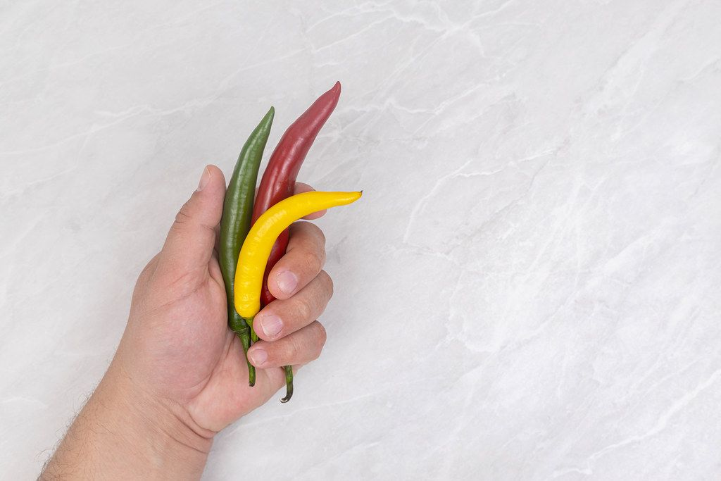 Chilli Peppers in the hand above table