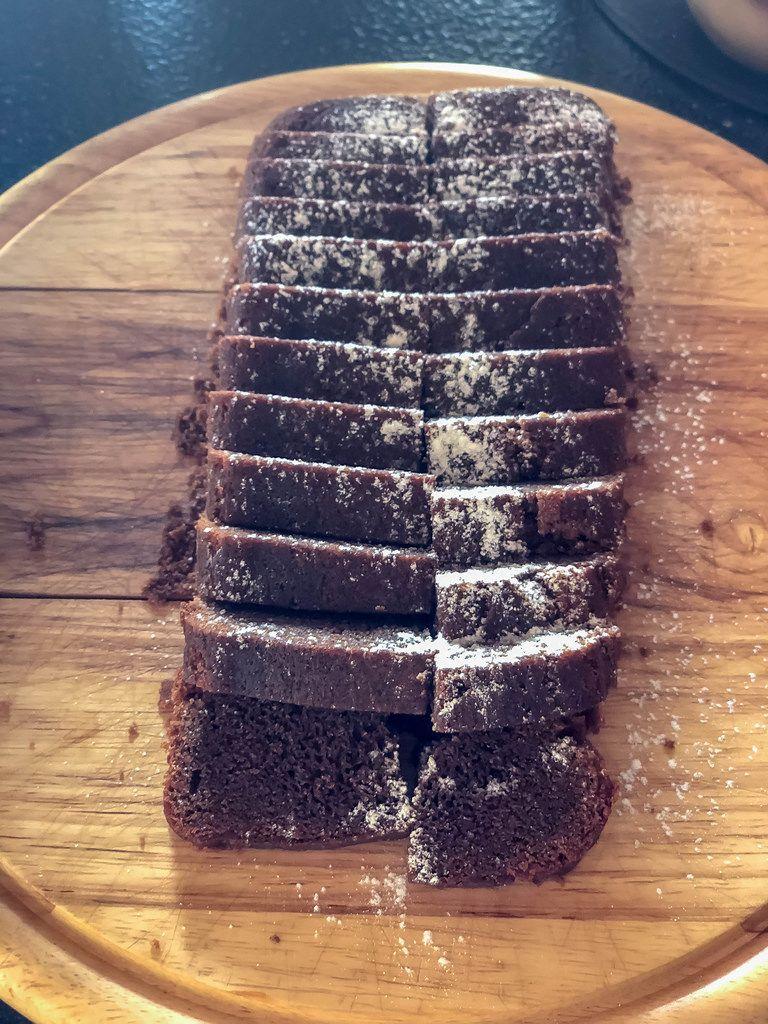 Chocolate cake with powdered sugar on a cutting board
