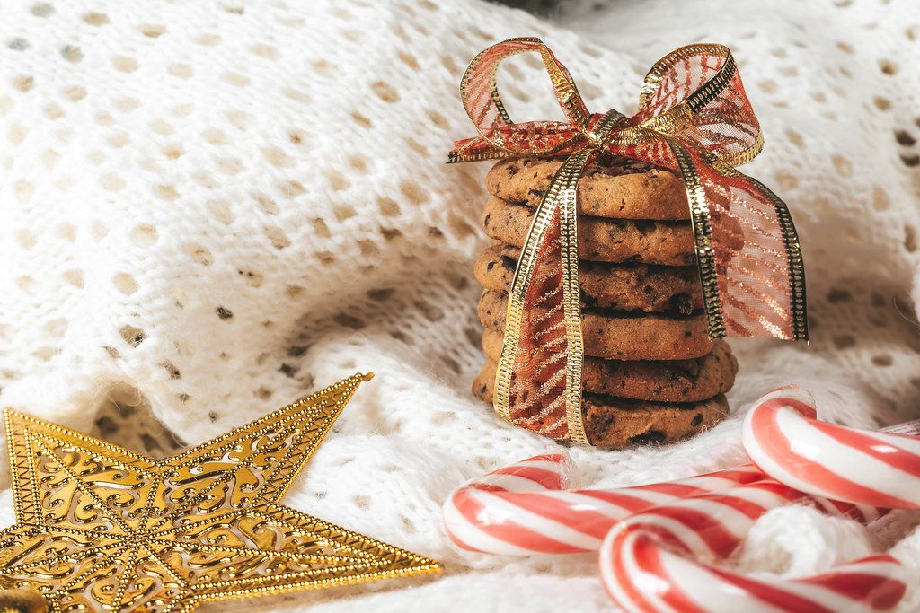 Chocolate chip cookies with Lollipop cane on white knitted background (Flip 2019)