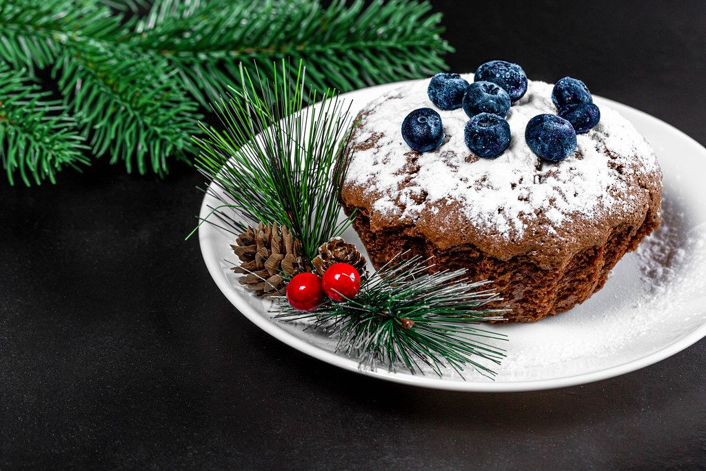 Chocolate cupcake with blueberries on a black background. Christmas dessert