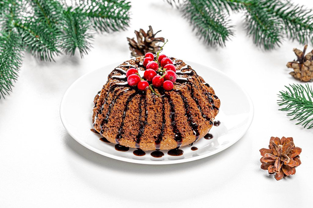 Chocolate cupcake with red currants on Christmas background