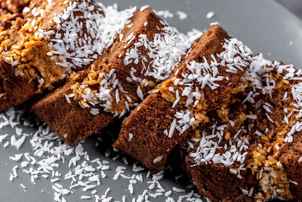 Chocolate sponge cake roll sprinkled with coconut