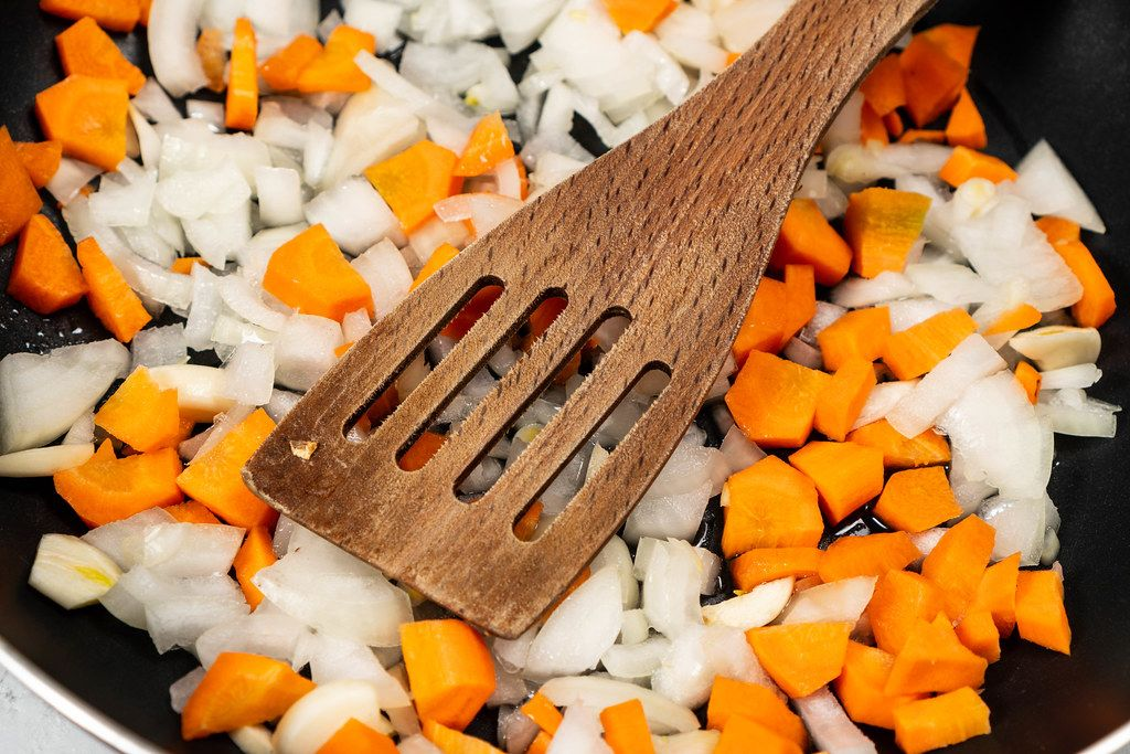 Chopped Carrots and Onions in the frying pan with wooden spoon