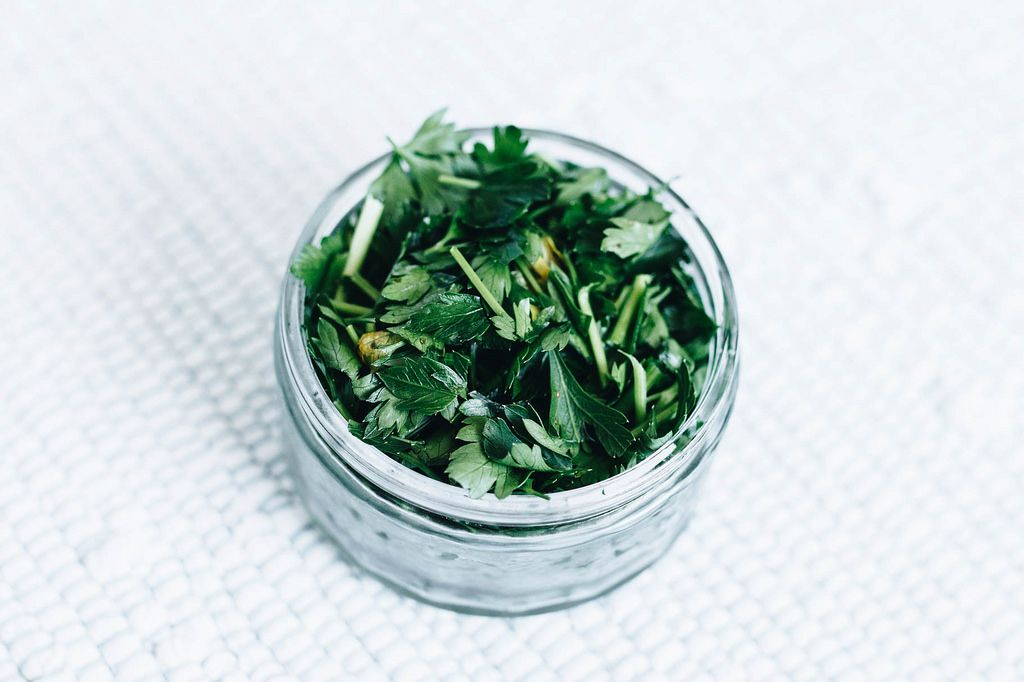 Chopped parsley in a jar . Close up