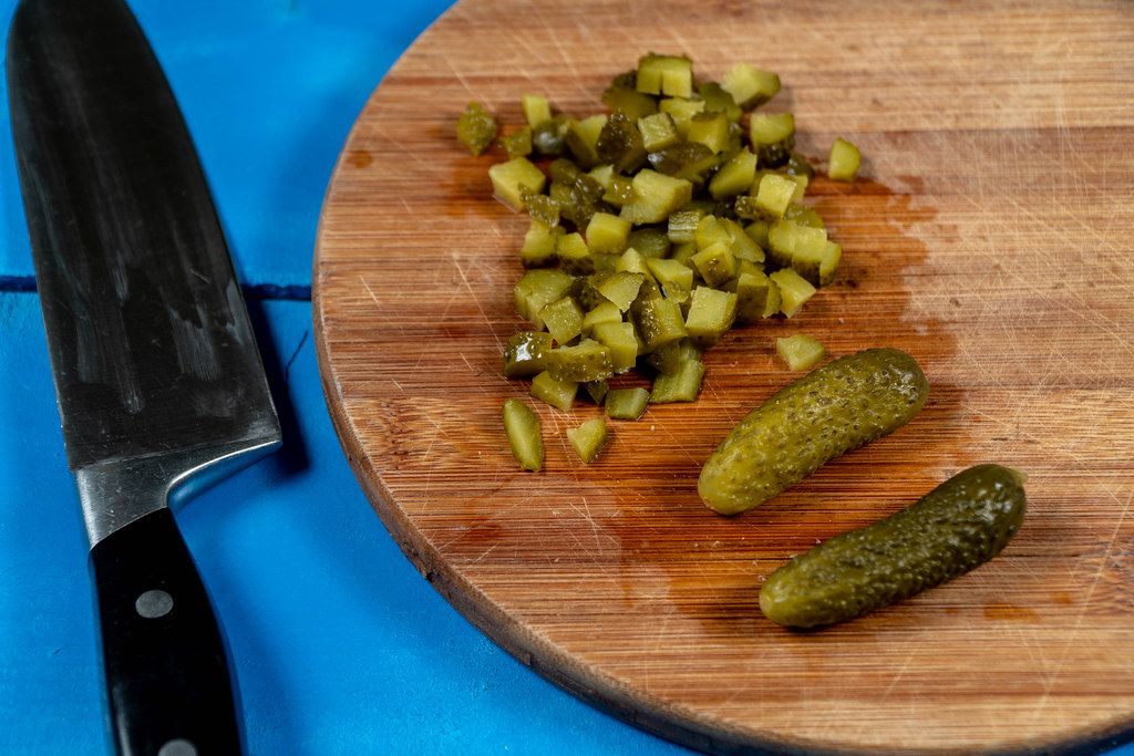 Chopped Pickles on the round wooden board with knife