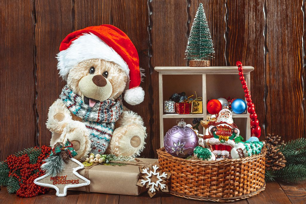 Christmas background with a teddy bear, Christmas toys and gifts on a wooden table. The concept of a children's holiday, family celebration