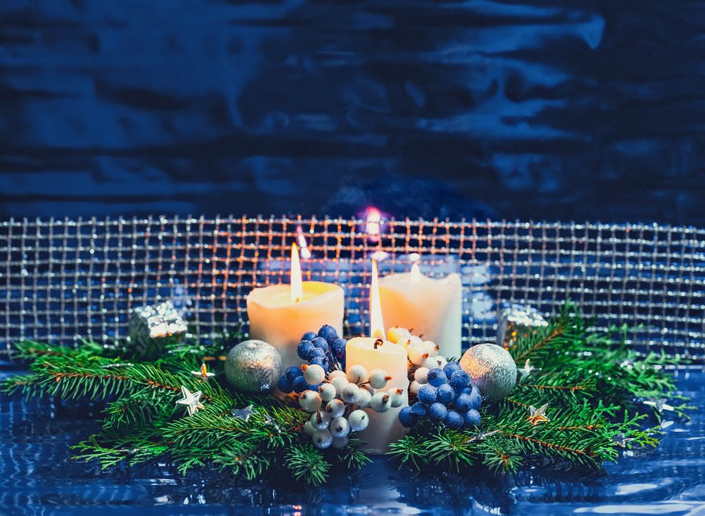 Christmas background with burning candles, Christmas tree branches, gifts and new year toys