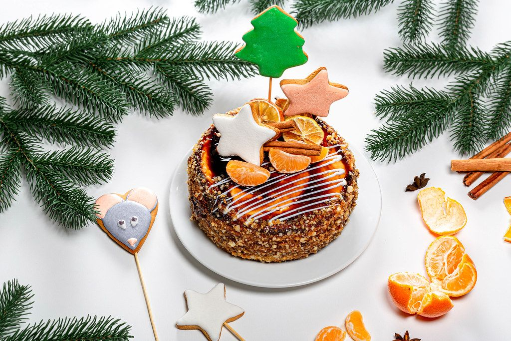 Christmas cake with gingerbread and tangerines on New year background