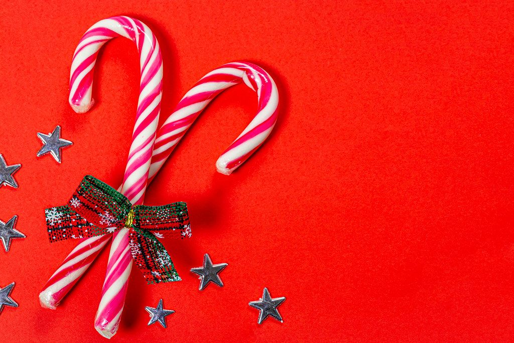 Christmas candy canes on a red background with stars (Flip 2019)