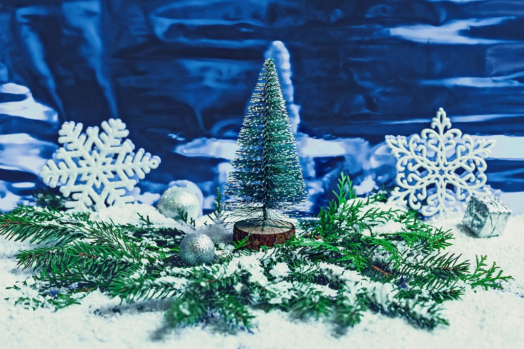 Christmas composition with Christmas tree on a snowy blue background.