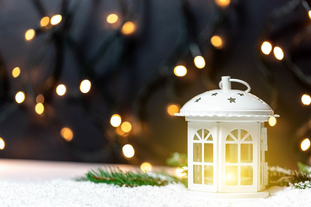 Christmas decoration: a white lantern placed on artificial snow with bokeh lights in the background