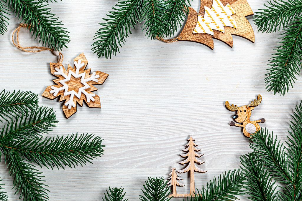 Christmas frame from wooden decorations and Christmas tree branches on a white wooden background