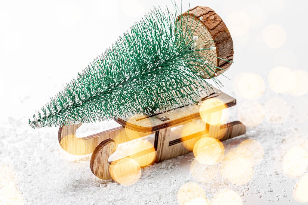 Christmas tree on a wooden sleigh on the background of snow. Christmas background with bokeh (Flip 2019)