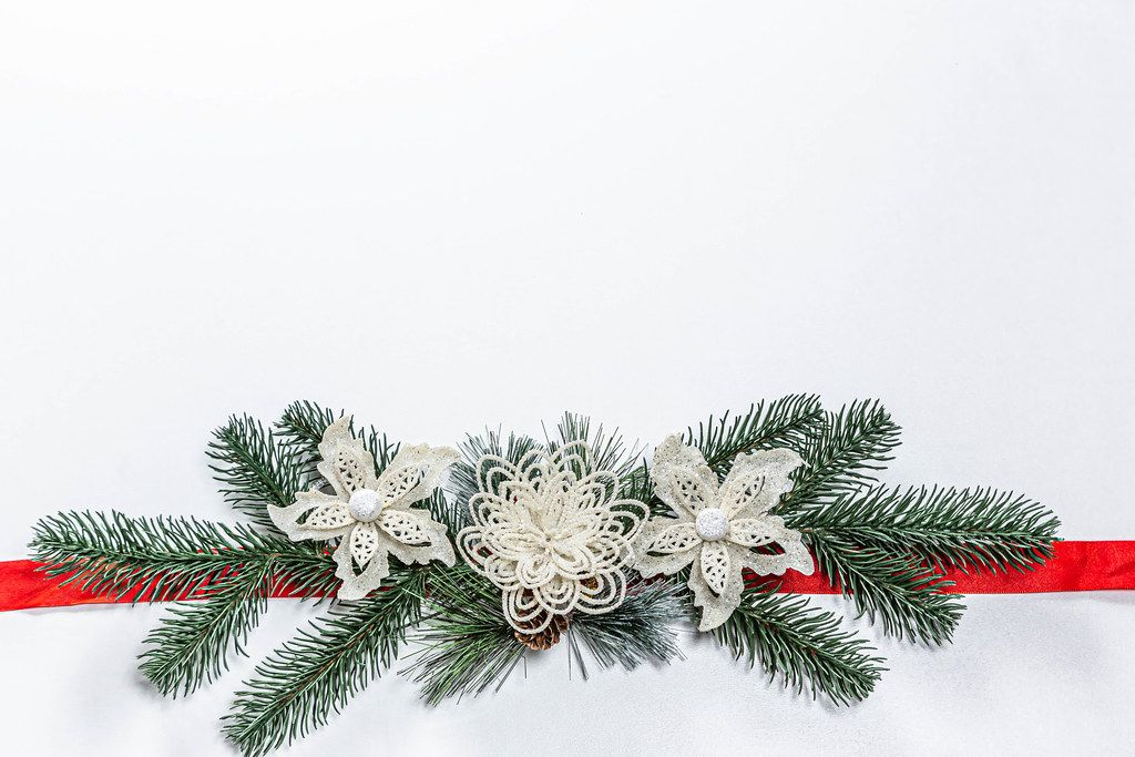 Christmas white background with Christmas tree branches, decor and red ribbon