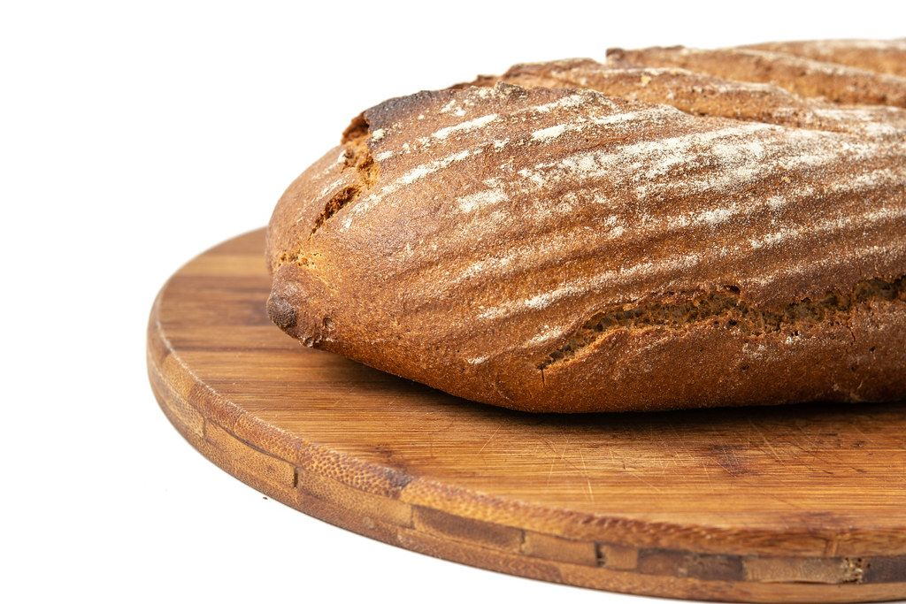 Chrono-Brot für eine gesunde Ernährung, liegt auf einem Holzbrett vor weißem Hintergrund